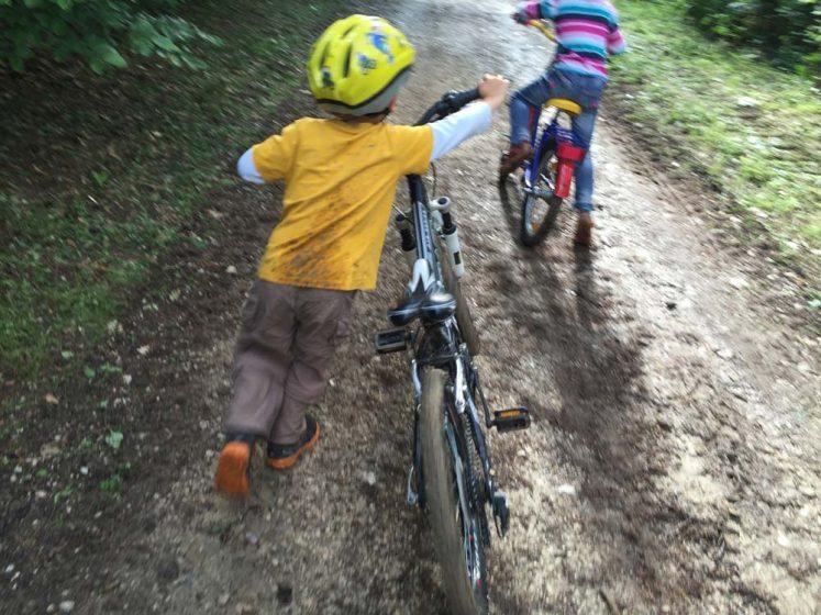 Kind schiebt Fahrrad im Wald beim Fahrradkurs für Kinder