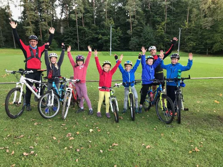 Kinder und Trainer heben die Hände hoch beim Fahrradkurs für Kinder