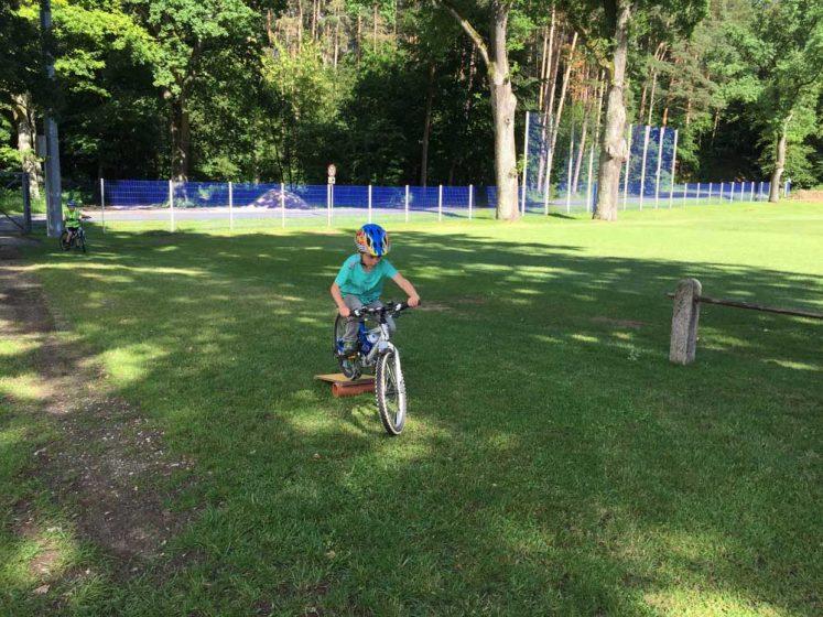 Ein Kind fährt über eine Wippe beim Fahrradkurs für Kinder