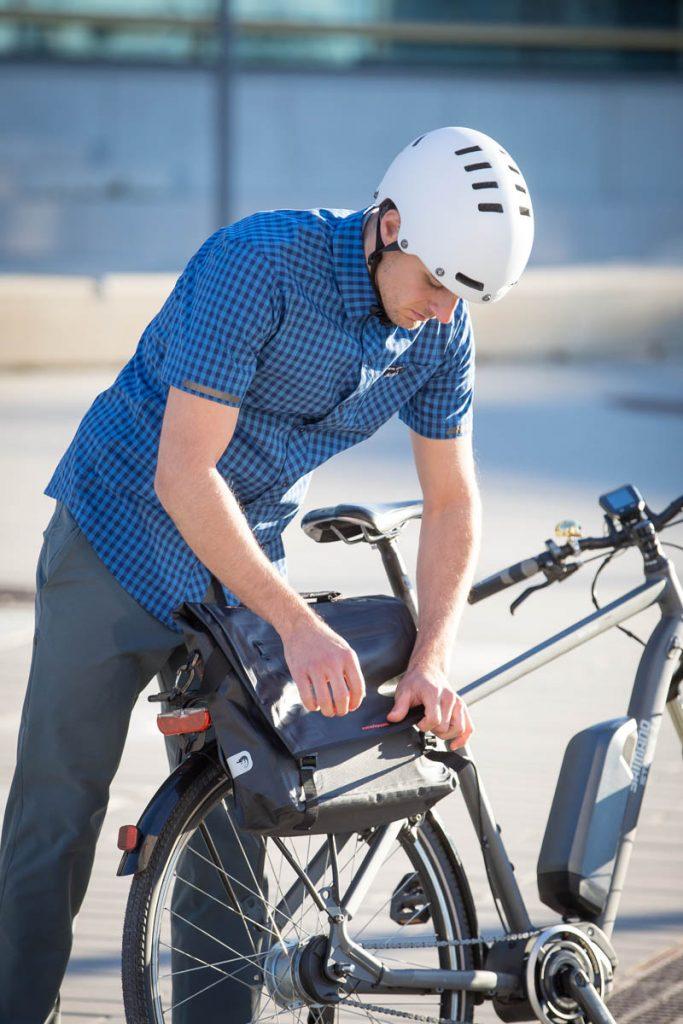 Pendler montiert seine Tasche am E-Bike