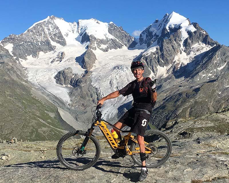 Майкл Тьюбер в горном путешествии со своим желтым Скоттом E-MTB с приводом SHIMANO.