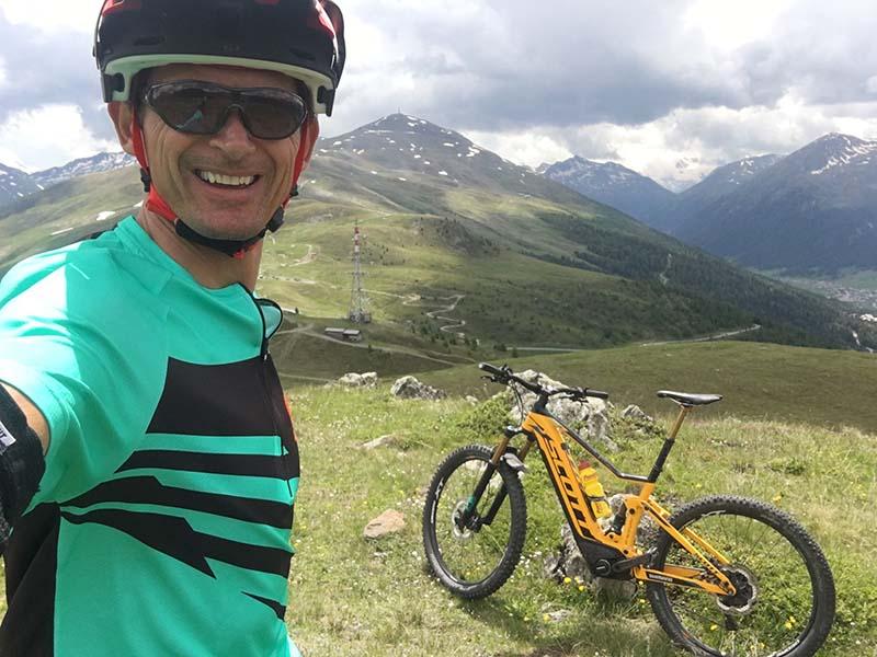 Майкл Тубер на лугу в горах со своим желтым Скоттом E-MTB с приводом SHIMANO.