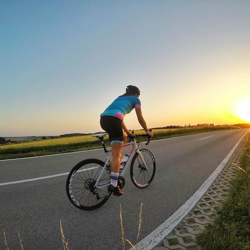 Frau fährt mit Rennrad entgegen Sonnuntergang