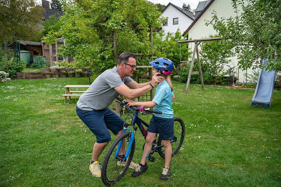 Fahrradhelm wird aufgezogen für Kind
