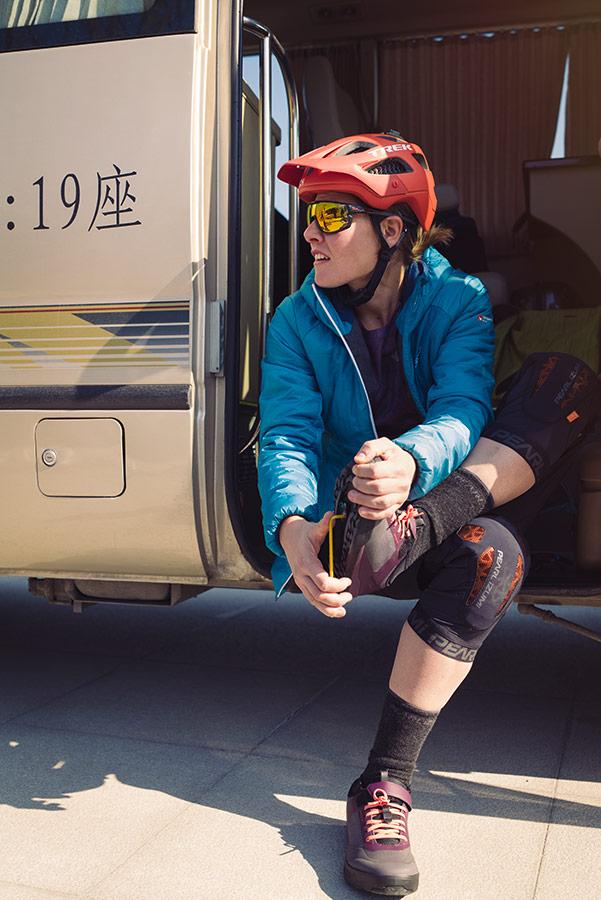 Nathalie Schneitter mit Protektoren beim Schuheausziehen im Bus