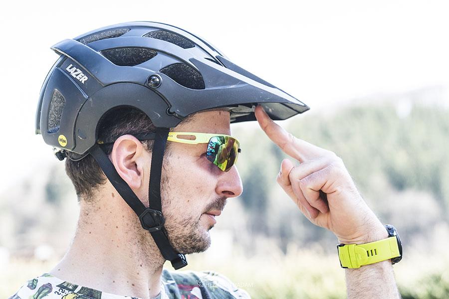 Mann mit Fahrradhelm auf dem Kopf drückt seinen Zeigefinger auf die Unterkante des Helmvisiers