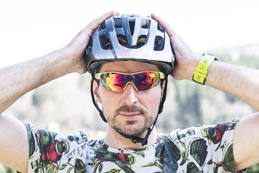 Mann mit Fahrradhelm auf dem Kopf zieht mit beiden Händen an seinem Helm